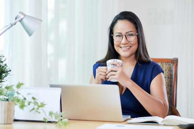 Alegre empresaria con café en el escritorio de trabajo