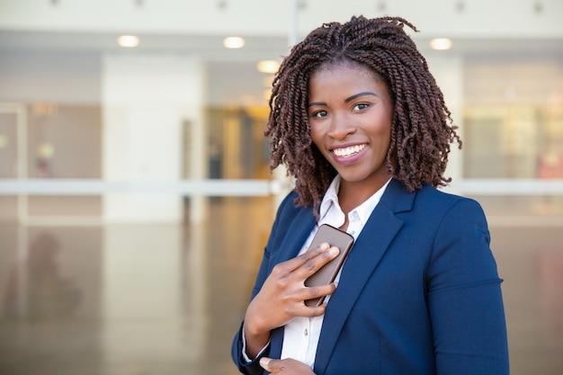 Alegre empresaria con celular recibiendo buenas noticias