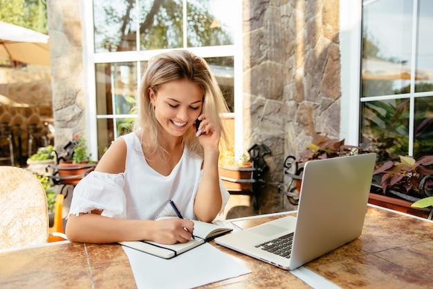 Alegre empresaria hablando por celular, mientras está sentado en el café.