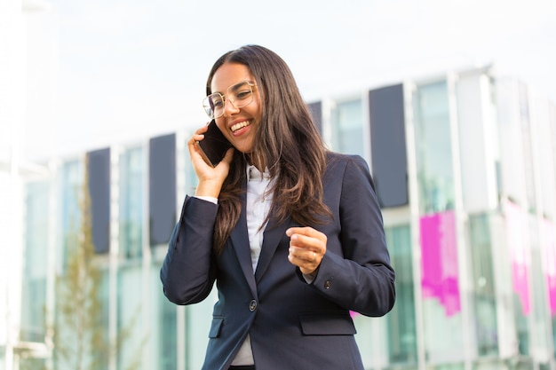 Alegre empresaria latina llamando al celular