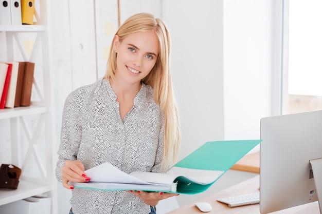 Alegre empresaria sonriente de pie y sosteniendo la carpeta en la oficina y mirando al frente