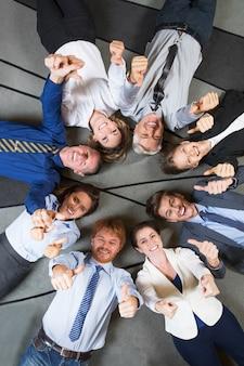 Alegre equipo de negocio exitoso con los pulgares arriba