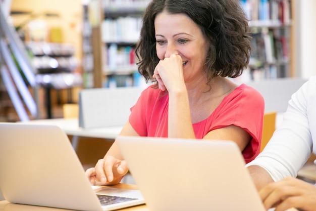 Alegre estudiante adulto disfrutando de contenido en computadora