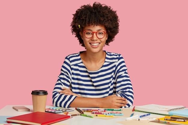 Alegre estudiante de raza mixta estudia arte en el lugar de trabajo
