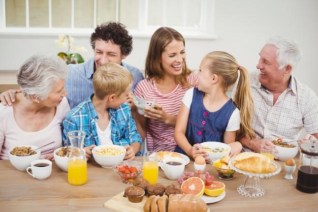 Alegre familia multigeneración desayunando