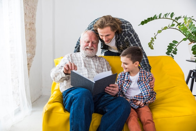 Alegre familia multigeneracional mirando a través del álbum de fotos.