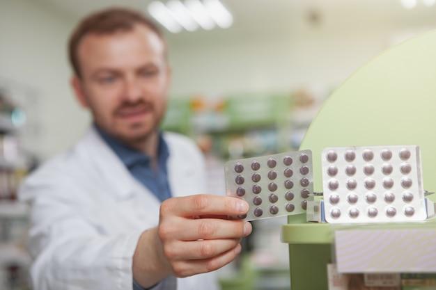 Alegre farmacéutico masculino maduro en la farmacia