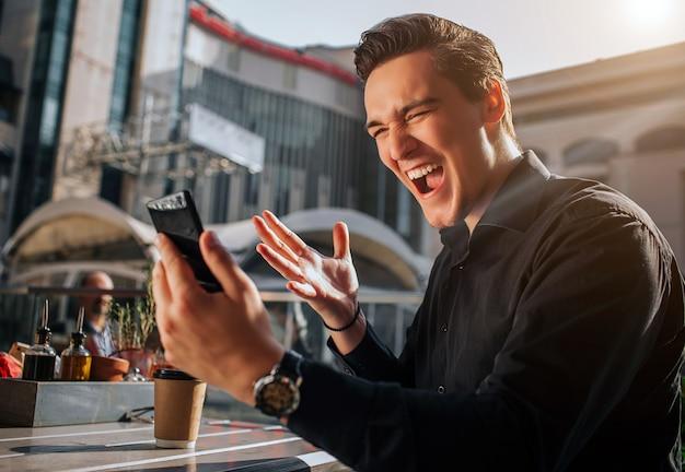 Alegre y feliz joven gritando. él es feliz. guy mira el teléfono. el se sienta afuera. hace sol.
