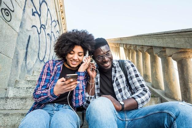 Alegre feliz pareja africana negra sentados juntos en amistad escuchando música desde un teléfono moderno y compartiendo los auriculares como socios. sonriendo y divirtiéndose