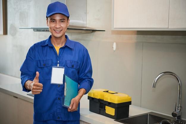 Alegre fontanero asiático de pie cerca del fregadero de la cocina y mostrando el pulgar hacia arriba