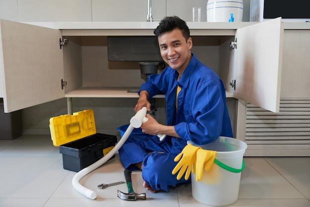 Alegre fontanero asiático sentado en el piso y reparando el fregadero de la cocina