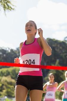 Alegre ganador atleta cruzando la línea de meta