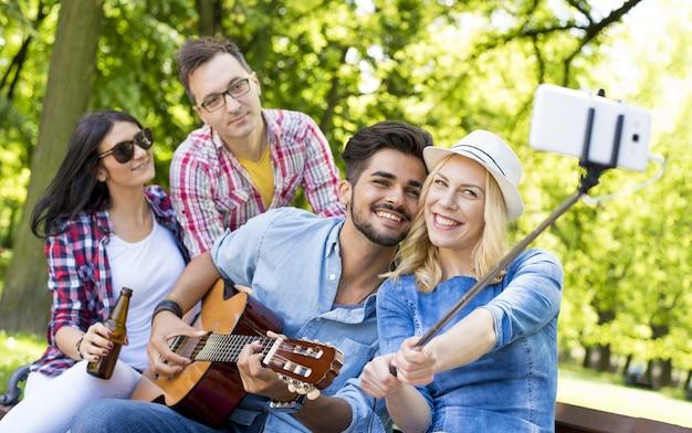 Alegre grupo de amigos caucásicos tomando un selfie con un palo selfie