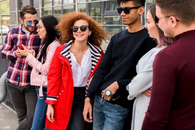 Alegre grupo de amigos de pie cerca del edificio