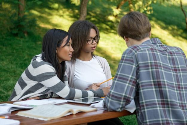Alegre grupo de jóvenes estudiantes sentados y estudiando