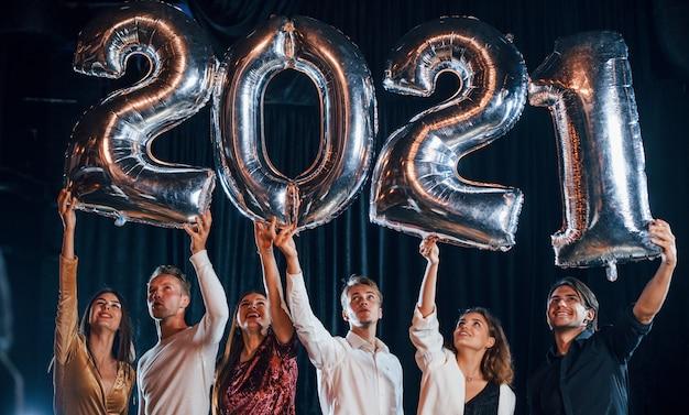 Alegre grupo de personas con bebidas y globos en las manos celebrando el nuevo año 2021.