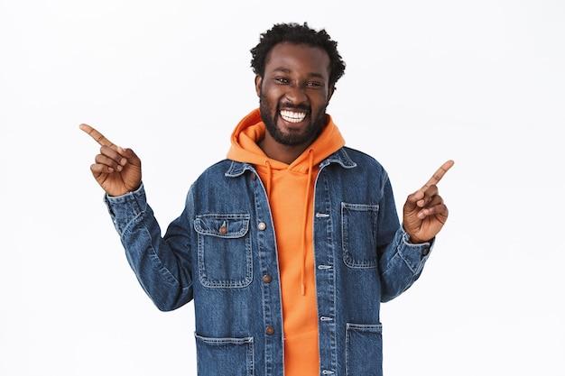 Alegre guapo afroamericano usa chaqueta de otoño de mezclilla, sudadera con capucha naranja, apuntando hacia los lados a la izquierda y a la derecha