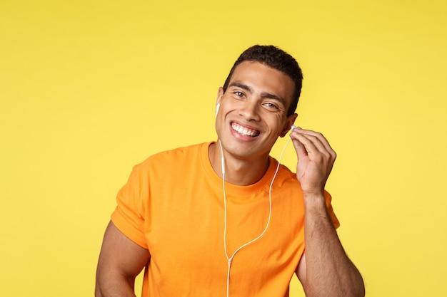 Alegre guapo atleta masculino en camiseta naranja coloca auriculares en el oído y sonríe