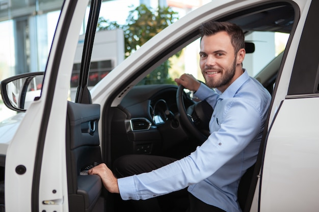 Alegre guapo conductor masculino sonriendo a la cámara, sentado en un auto nuevo en el concesionario