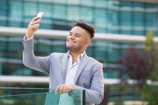 Alegre guapo interno fotografiando a sí mismo