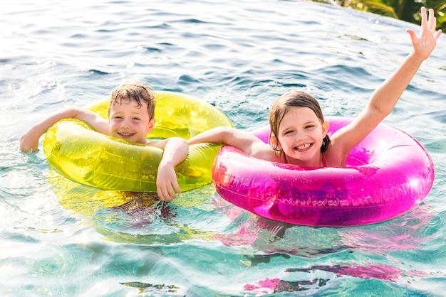 Alegre hermano y hermana nadando en la piscina