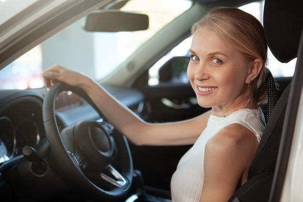 Alegre hermosa conductora sonriendo a la cámara desde su automóvil