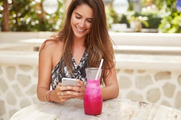 Alegre hermosa dama con lujoso cabello oscuro feliz de recibir notificaciones en el teléfono móvil, mensajes de texto, rodeada de batidos frescos, disfruta de conexión gratuita a internet en la cafetería