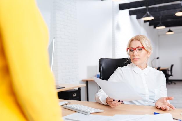 Alegre hermosa empresaria madura entrevistando al candidato para un nuevo puesto en la oficina