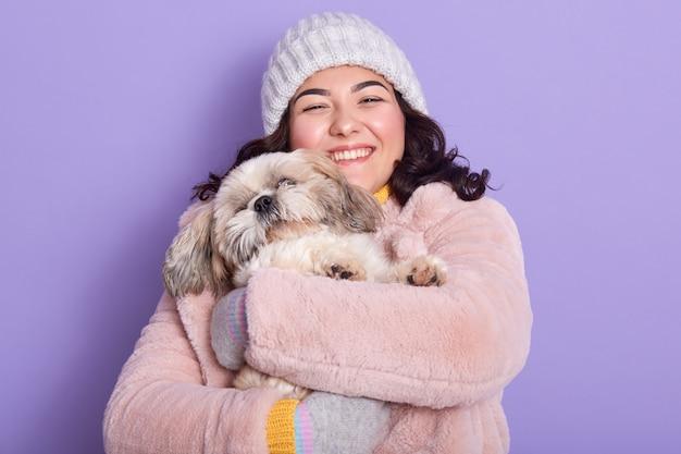 Alegre hermosa joven sosteniendo a su perro en ambas manos