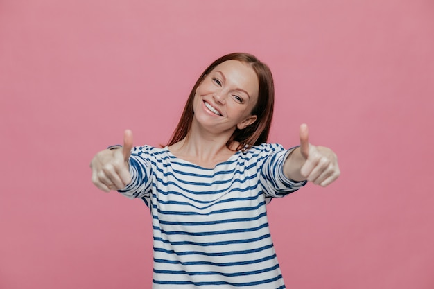 Alegre hermosa jovencita levanta los pulgares a la cámara, muestra que todo está bien
