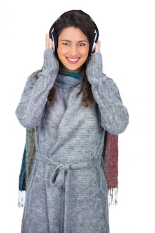 Alegre hermosa modelo vistiendo ropa de invierno escuchando música