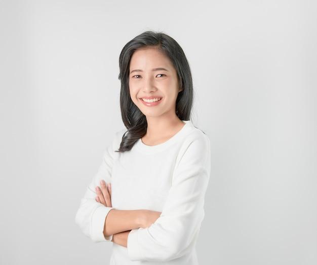 Alegre hermosa mujer asiática de pie y brazos cruzados