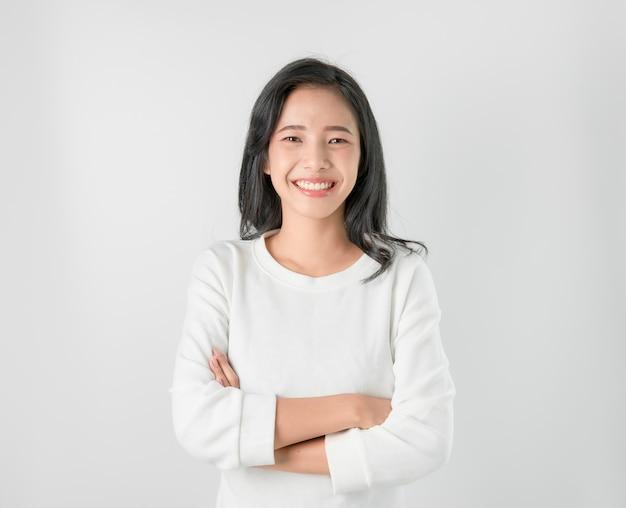 Alegre hermosa mujer asiática soporte y brazos cruzados en gris.