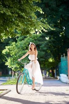Alegre hermosa mujer joven en bicicleta en el parque en un día soleado de verano