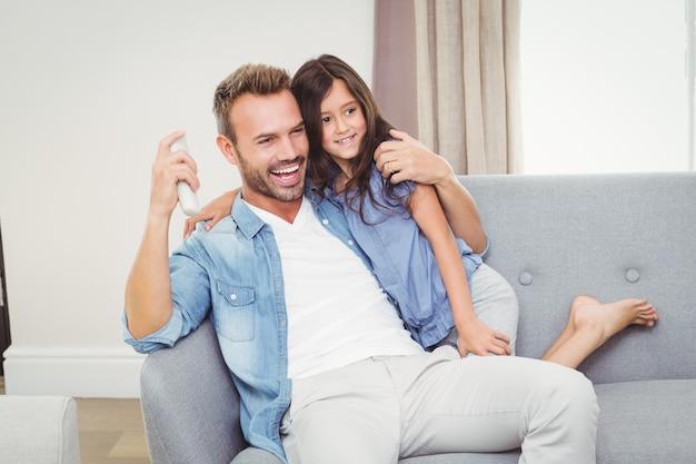 Alegre hija y padre viendo televisión