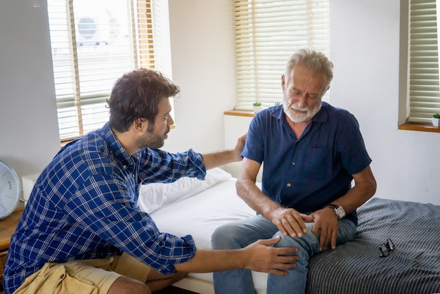 Alegre hombre adulto cuidando anciano en casa