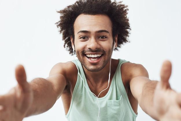 Alegre hombre africano en auriculares sonriendo estirando la mano