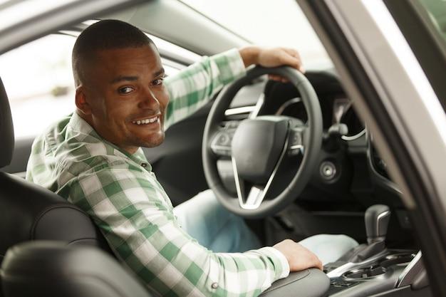 Alegre hombre africano sonriendo a la cámara, sentado en su auto nuevo en el concesionario.