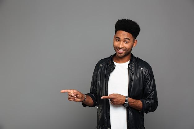Alegre hombre afroamericano en chaqueta de cuero apuntando con dos dedos, mirando