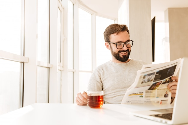 Alegre hombre barbudo europeo con gafas sentado a la mesa y beber té de vidrio, mientras lee el periódico en la mañana
