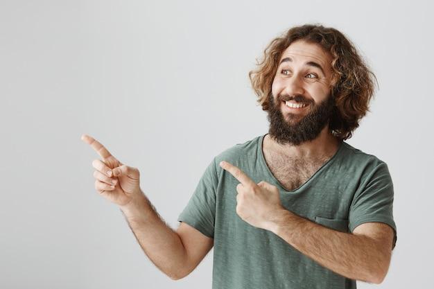 Alegre hombre barbudo del medio oriente que señala el dedo en la esquina superior izquierda con una sonrisa complacida