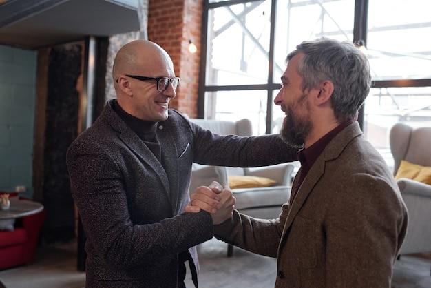 Alegre hombre calvo en gafas apretón de manos con un amigo mientras está emocionado de verlo en su propia casa