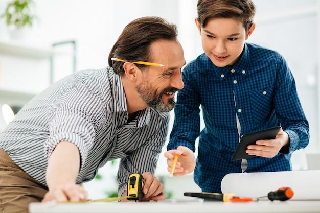 Alegre hombre de mediana edad midiendo la longitud con cinta métrica y su concentrado en sostener una tableta moderna y apuntando a la mesa