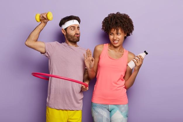 Alegre hombre motivado con barba incipiente, gira hula hoop, entrena los músculos con mancuernas y mujer afro insatisfecha hace gesto de rechazo, sostiene una botella de agua