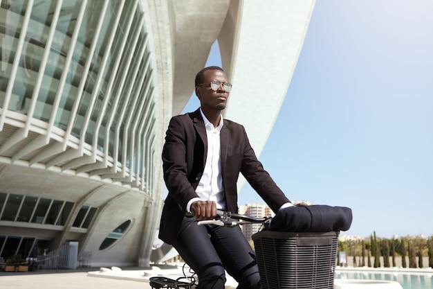 Alegre hombre de negocios masculino europeo negro elegante que usa la bicicleta para llegar a la oficina mientras su automóvil está roto, en bicicleta en un entorno urbano, pasando por edificios modernos y una fuente en un día soleado de verano