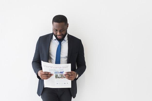 Alegre hombre de negocios negro con periódico