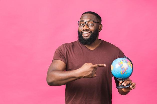 Alegre hombre negro afroamericano sosteniendo el globo con amor y cuidado aislado sobre fondo rosa. concepto de viaje, buscando un viaje.