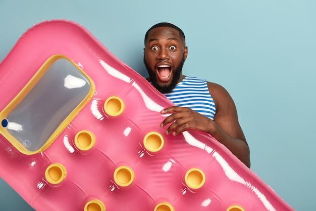 Alegre hombre sorprendido con cuerpo musculoso, sostiene un colchón inflable rosa para nadar, va a relajarse en el agua, descansa en un balneario