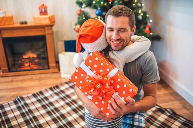 Alegre joven abrazando a su hijo y sonriendo.