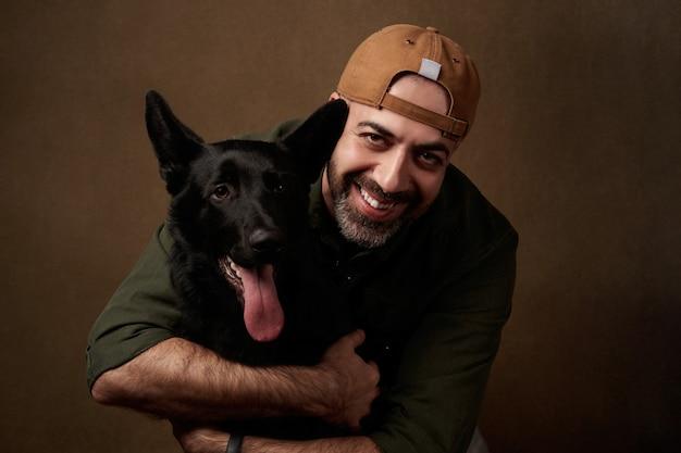 Alegre joven abrazando a su perro, en interiores retrato